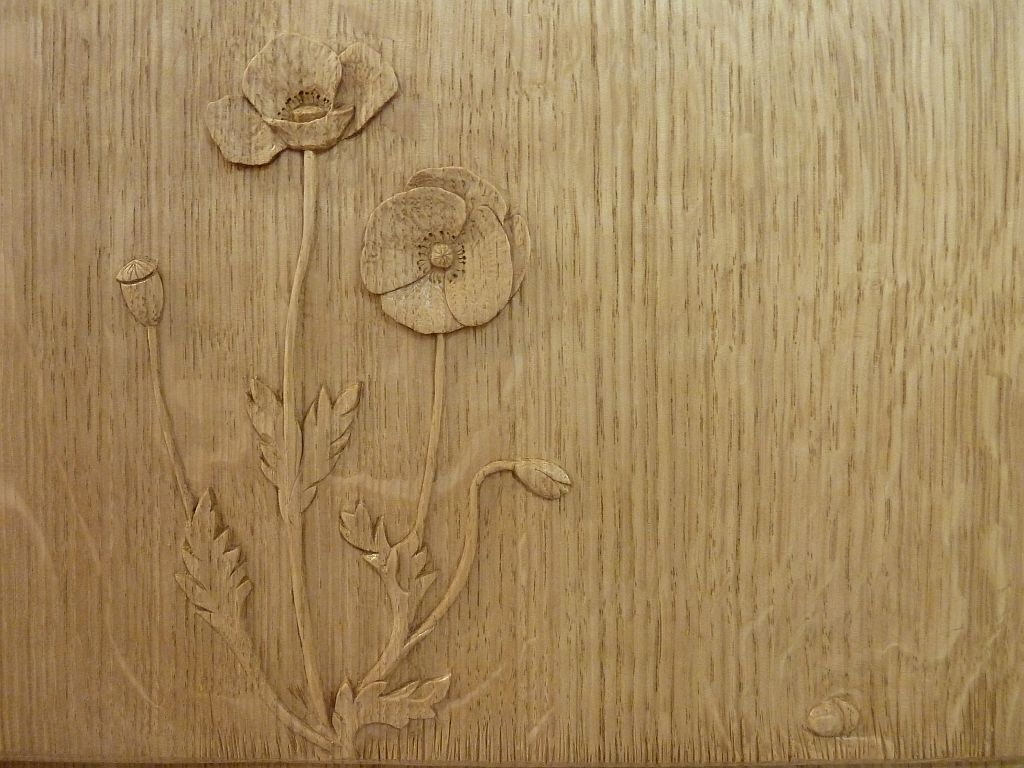 Poppy carving in wooden bookcase end panel